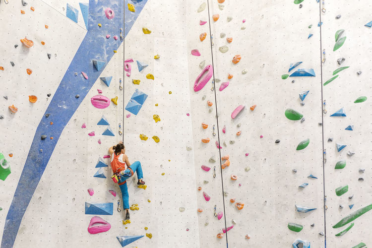 Low angle view of woman climbing on wall