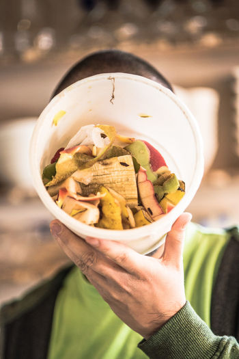 Man Covering Face With Fruit Peels In Container