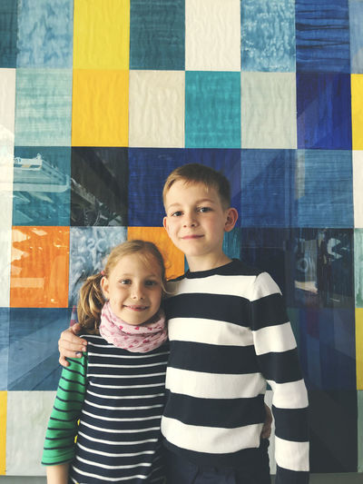 Portrait of smiling siblings standing against wall