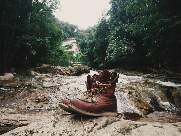 Shoes on rock against stream at forest