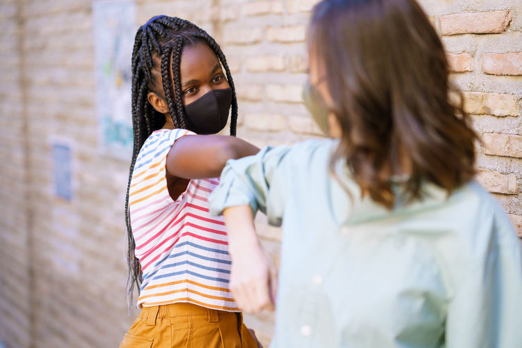 Young women wearing mask doing elbow bump outdoors