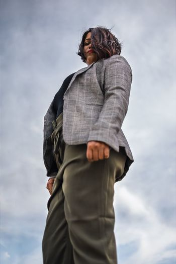 Low angle view of businesswoman standing against sky