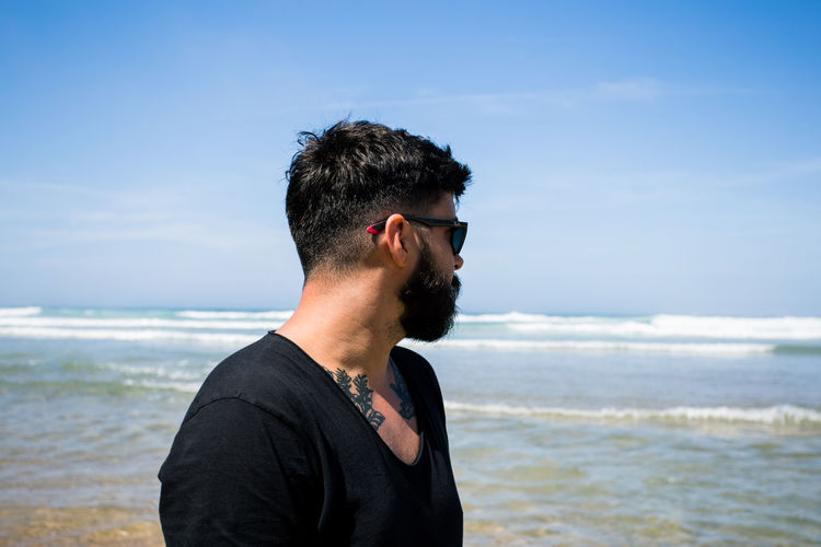 Beard Tattoo Sea Water Land Sky Beach One Person Leisure Activity Young Adult Sunglasses Glasses Young Men Lifestyles Nature Real People Headshot Horizon Over Water Horizon Fashion Outdoors