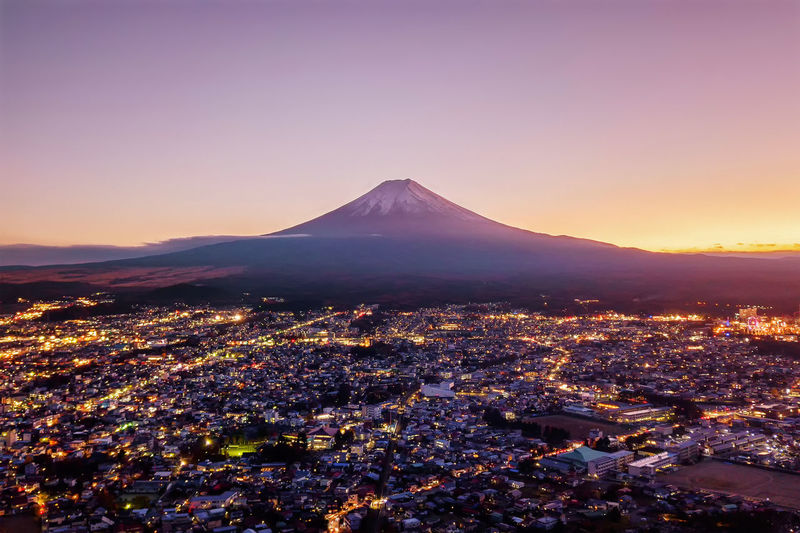 Aerial view of Fuji mountain at sunset in Fujikawaguchiko, Yamanashi. Urban city, Japan. Landscape with architecture buildings Fuji Mountain Cityscape City Urban Skyline Skyline Sunset Japan Volcano Sky Travel Destinations Mountain Peak Nature Scenics - Nature No People Architecture Beauty In Nature Building Exterior Landscape Environment Land Outdoors Travel Snowcapped Mountain