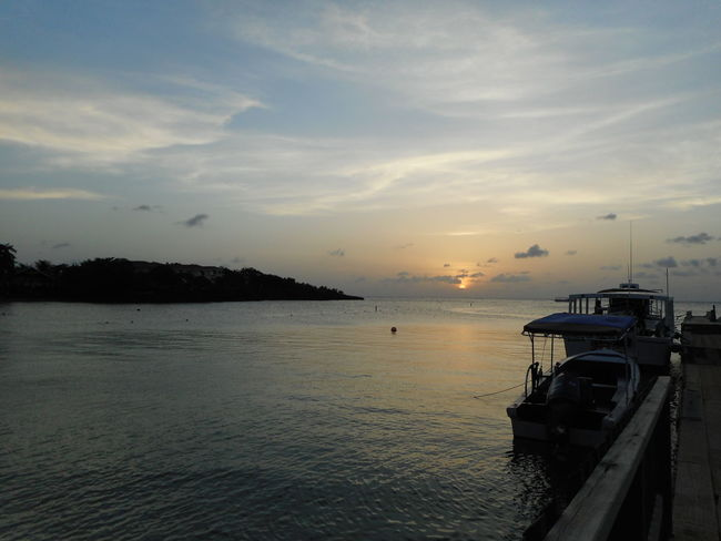 Honduras Roatan Bay Islands Beauty In Nature Boat Cloud - Sky Cruise Ship Day Freight Transportation Harbor Mode Of Transport Moored Nature Nautical Vessel No People Outdoors Sailing Scenics Sea Ship Sky Sunset Transportation Water