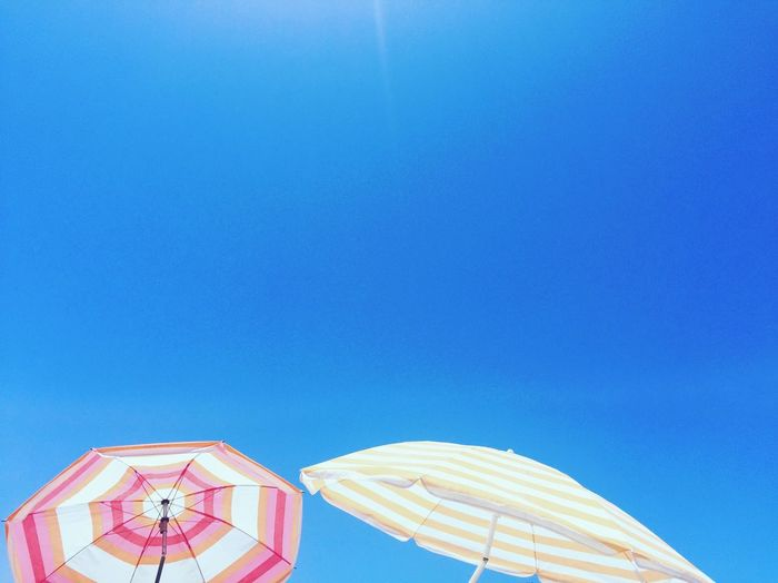 Low Angle View Of Umbrellas Against Clear Blue Sky