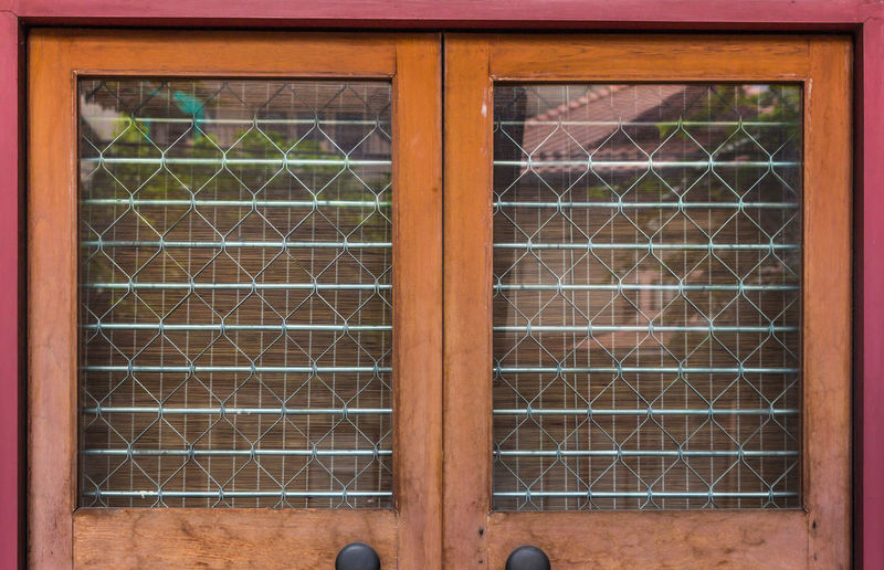 Retro doors of antique shop make from wood frame, cage, blind and glass. Abandoned Backgrounds Bad Condition Brick Wall Closed Design Deterioration Doors Fence Full Frame Geometry Glass Glass - Material Interior Metal No People Obsolete Pattern Protection Retro Safety Symmetry Transparent Wall Window