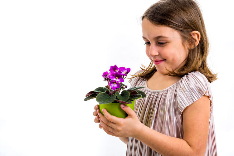 Indoors  One Person Girl Child Little Children Dress Hair Flower Flower Head Potted Plant Pot Portrait Viola Viola Flowers Violet Violet Flowers Plant Violaceae Looking Holding Green Smelling Smelling The Flowers Expression Emotion Face White White Background Isolated Emotions Hands Studio Shot Lifestyles Freshness Girls Woman Purple Fresh