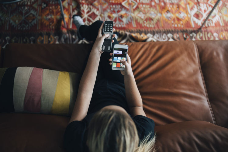 Rear view of man using mobile phone on sofa at home