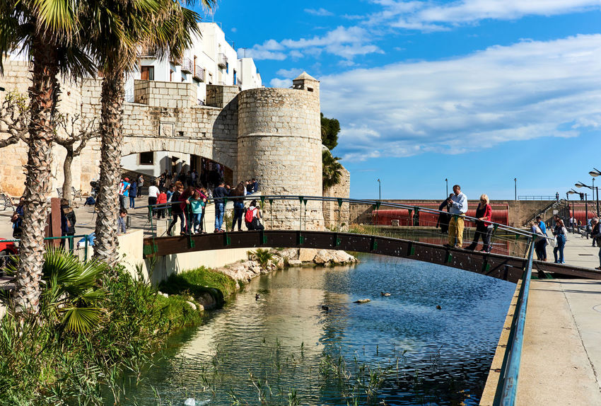 Peniscola, Spain - March 3, 2016: View to the old town of Peniscola. Costa del Azahar, province of Castellon, Valencian Community. It is a popular tourist destination in Spain Ancient Architecture Bridge Building Exterior Castellón Castillo Del Papa Luna City Costa Del Azahar Editorial  Europe Fort Fortress Landscape Large Group Of People Old Town Outdoors People Peñíscola Pond SPAIN Sunny Day Tourism Tourists Travel Destinations Water