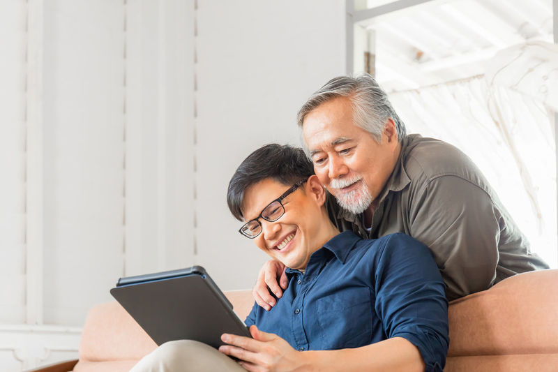 Man and woman using smart phone while sitting on laptop