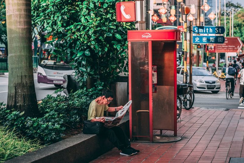 What's he reading? Vibes Chinatown Urban Bicycle Street Photography Street Old Man Reading Newspaper Telephone Telephone Booth Red Crush Red Outdoors Day Full Length Real People City Sitting Women Tree Adult People