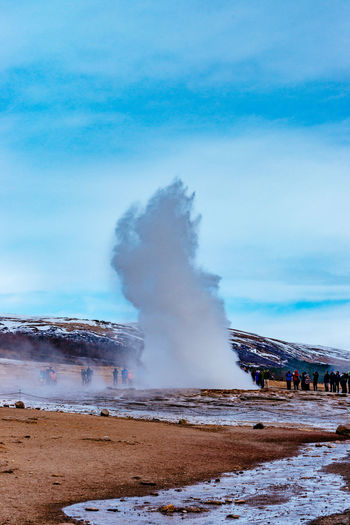 People Looking At Splashing Geyser Against Sky