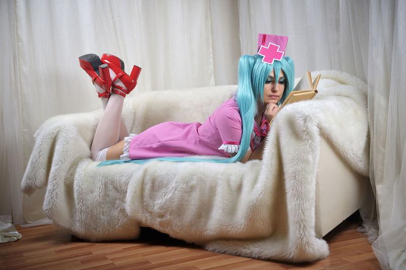 Women wearing nurse costume reading book while lying on sofa