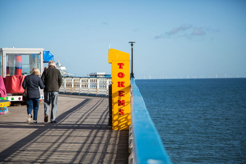 Couple walking on Llandudno pier north wales Rear View Sky Water Men Real People Sea Two People Lifestyles Nature Architecture People Built Structure Full Length Walking Leisure Activity Adult Day Women Outdoors Horizon Over Water Couple - Relationship Llandudno Pier Wales UK Tokens Moments Of Happiness