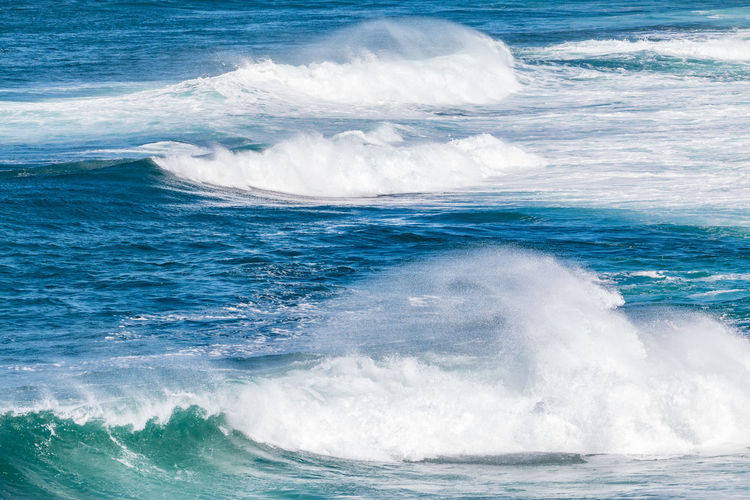Blue ocean water with white waves in late afternoon