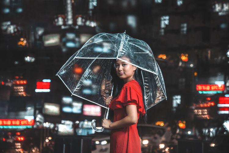 Woman standing on wet illuminated city during rainy season at night