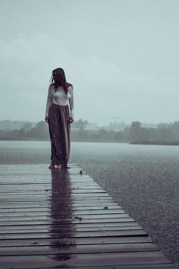 Full Length Of Woman Standing On Pier By Lake Against Sky
