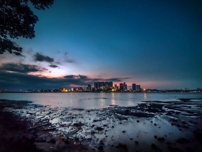 Scenic view of sea with urban skyline in background against sky at dusk