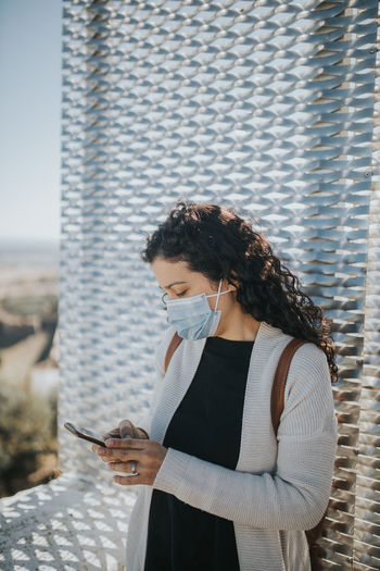 Side view of young woman using mobile phone with mask