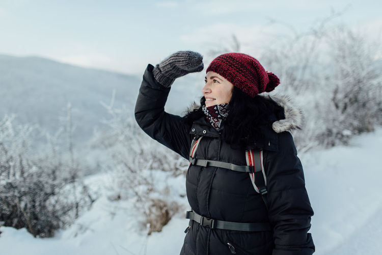 Smiling Woman In Warm Clothing Shielding Eyes While Standing On Snowcapped Mountain