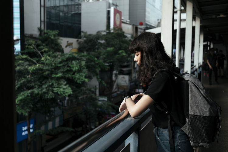 Side view of young woman standing by railing in balcony
