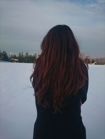 Rear view of woman on snow covered field