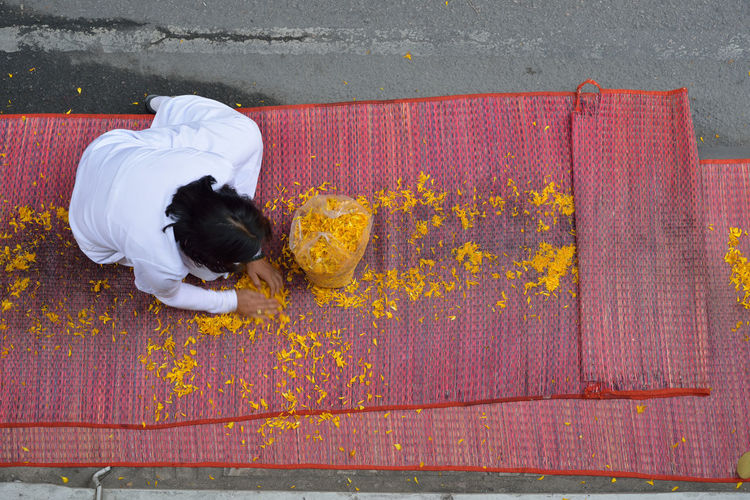 High angle view of woman collecting flower petals on mat
