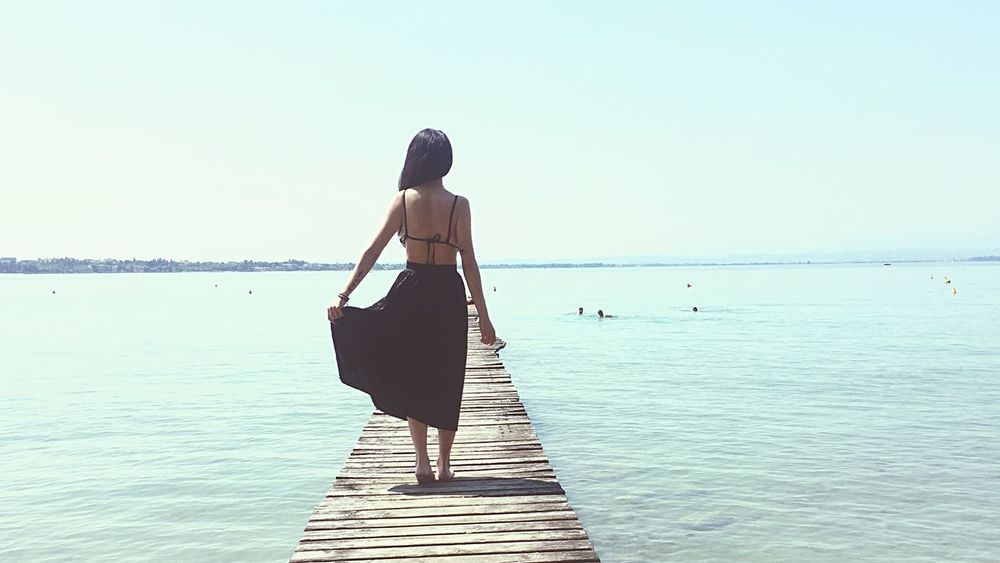 Rear View Sea Water Full Length Standing One Person Real People Nature Outdoors Lifestyles FreeTime PeschieraDelGarda Lake Lake View Garda Wood - Material Beauty In Nature Clear Sky Walking Women Scenics Day Sky Summer Fashion Stories