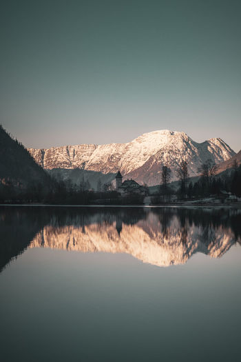 Scenic view of lake by mountains against clear sky during winter