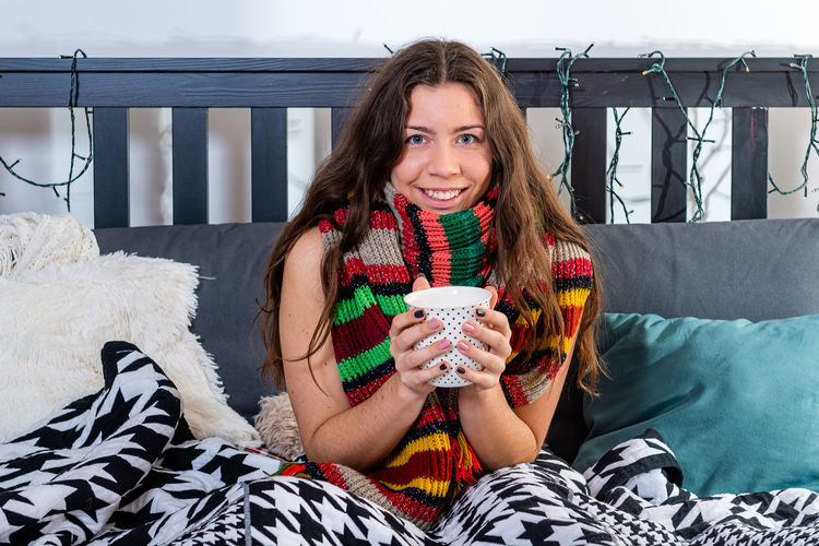 Portrait of smiling young woman sitting on bed