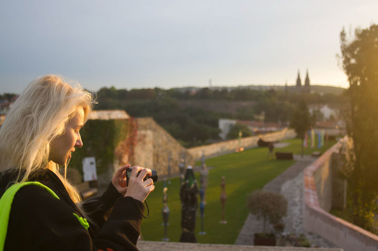 side view portrait of woman holding camera against sky Adult Architecture Blond Hair Focus On Foreground Hair Hairstyle Headshot Holding Leisure Activity Lifestyles Nature One Person Outdoors Portrait Real People Side View Sky Women Young Adult Young Women