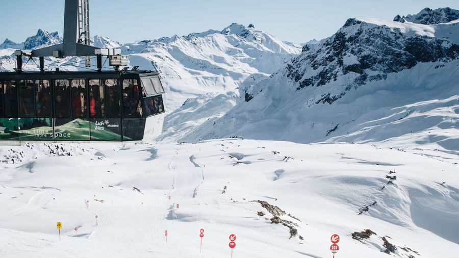 Aerial view of ski lift over snowcapped mountains against sky