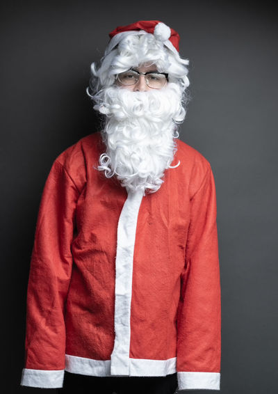 portrait of awkward santa claus with oversized costume in front of grey background Studio Shot Portrait Standing Awkward Clumsy  Santa Claus Oversized Gift Christmas Xmas Gray Background Silly Costume Celebration Holiday - Event Beard Red One Person Confused Front View