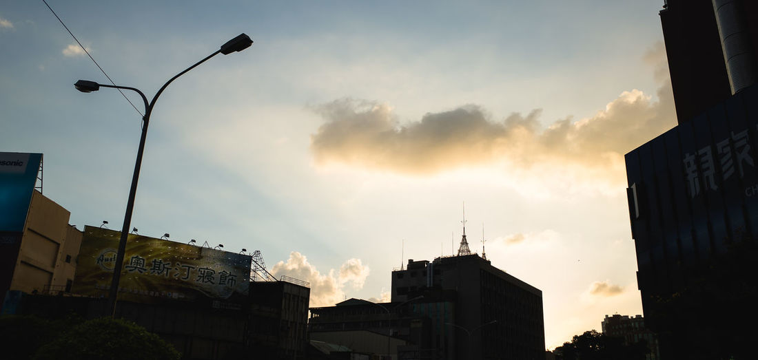 Low Angle View Of Silhouette Street Light And Buildings Against Sky During Sunset