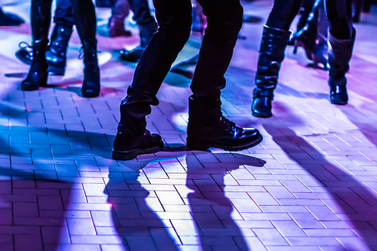 Low section of people dancing on illuminated floor