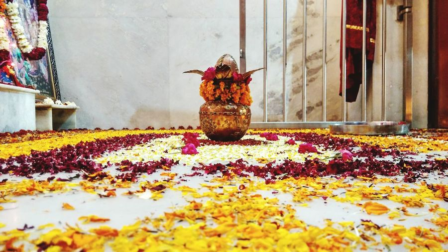 Decorated kalash on petals covered floor at home