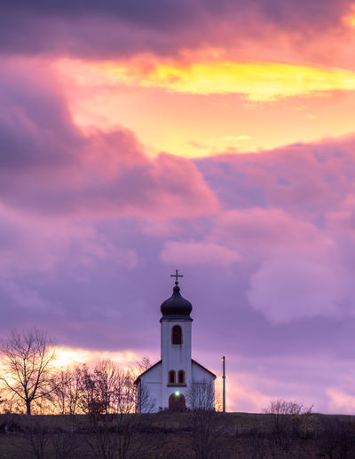 Church by building against sky during sunset