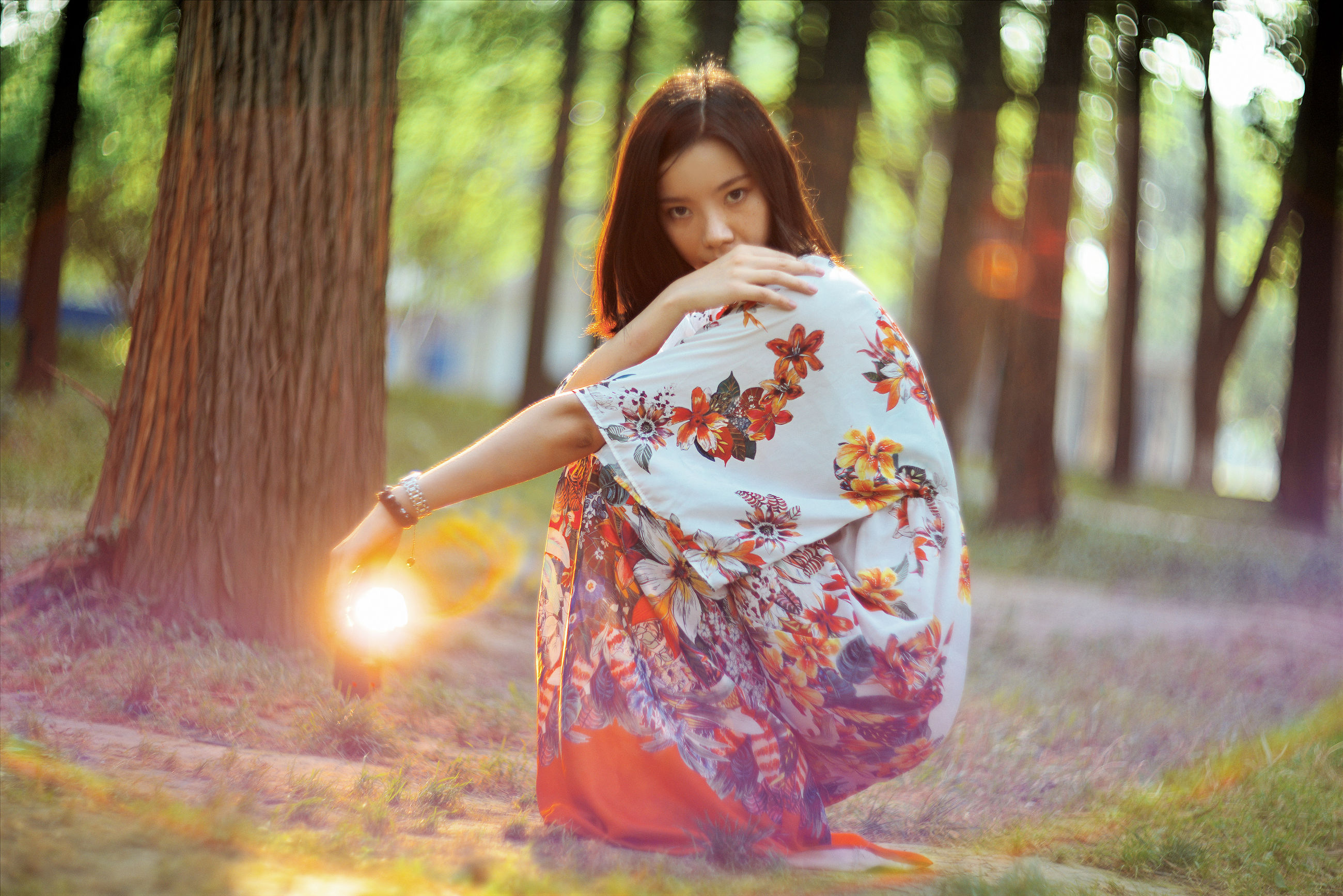 tree, focus on foreground, lifestyles, leisure activity, front view, casual clothing, standing, person, forest, sunlight, outdoors, day, childhood, lens flare, park - man made space, looking at camera, full length, portrait