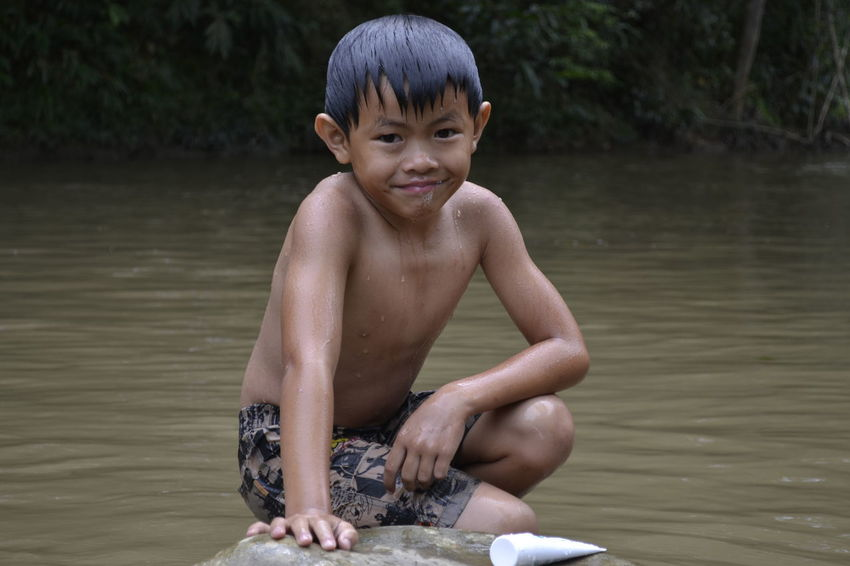 Portrait Water Sitting Lifestyles Smiling Boys People Childhood Fun Nature Village Life Outdoors Day BARIO Village People Kids Playground Village Photography Family Vacation Looking At Camera