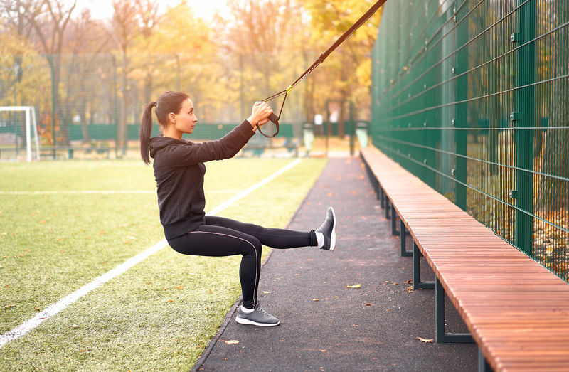 Side view of woman exercising with strap in public park