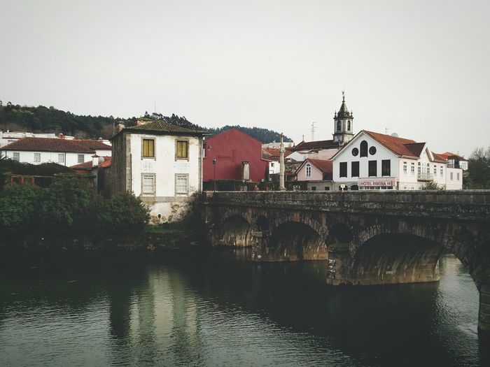 Buildings and bridge over vez river in arcos de valdevez against sky