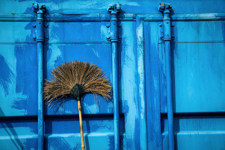 Hard broom leaning up against blue metal wall of container house, closeup and selective focus. No People Blue Day Metal Wall - Building Feature Architecture Close-up Built Structure Cleaning Building Building Exterior Cleaning Equipment Wood - Material Outdoors Hygiene Broom Clean Accessory Simple Sanitation Tools Typical Household Düster Broomstick