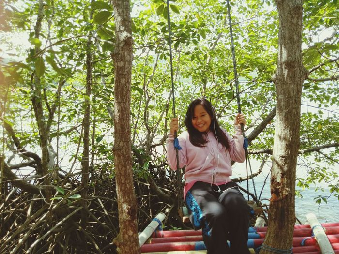 Smiling woman swinging on swing in forest