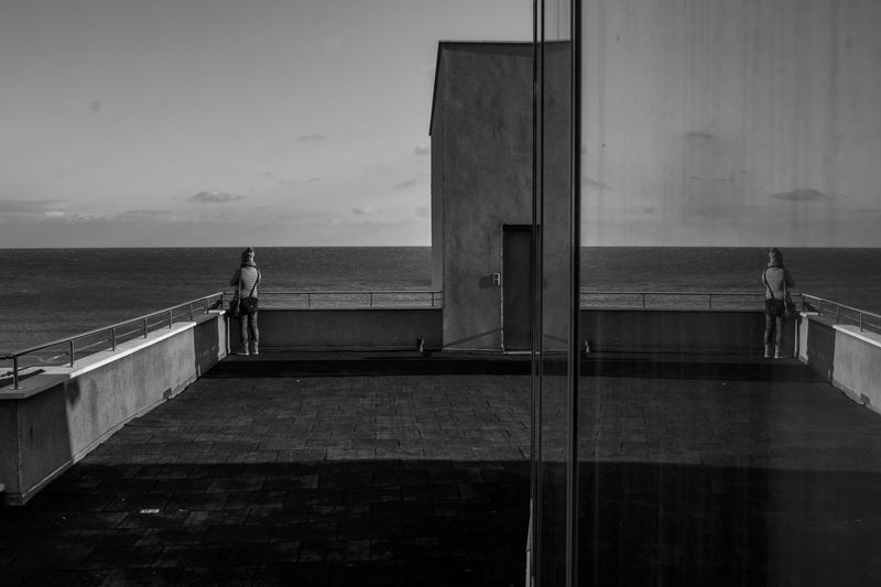 Reflection of woman standing by railing while looking at sea against sky