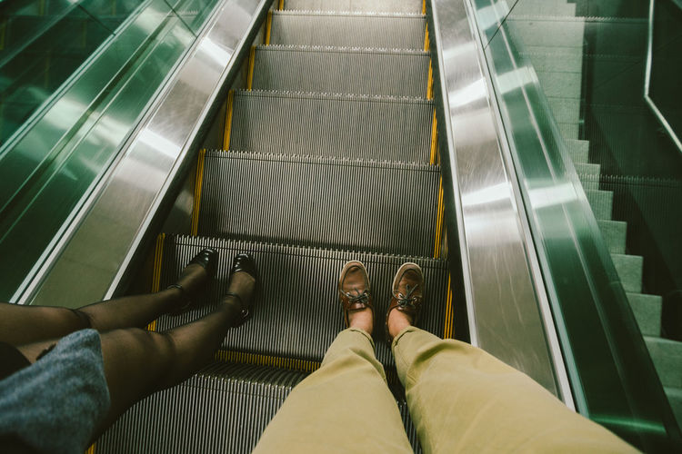 Low section of women standing on escalator