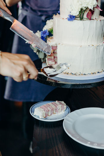 Cropped Hands Serving Cake In Plate At Wedding Ceremony