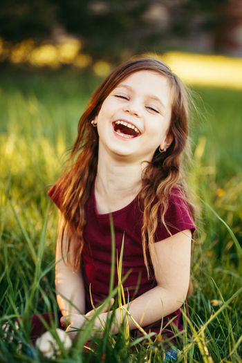 Cheerful girl sitting on field