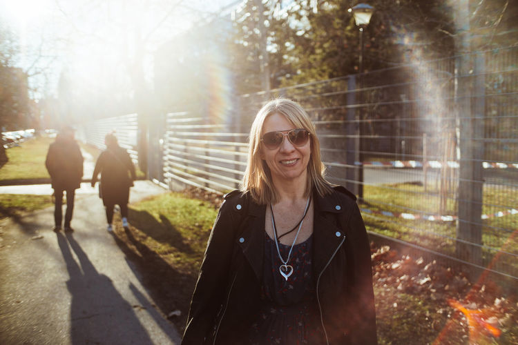 Portrait of smiling woman wearing sunglasses standing in park