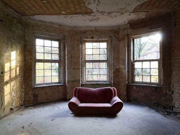 Interior of abandoned house with bis windows, light reflection on a wall and a sofa